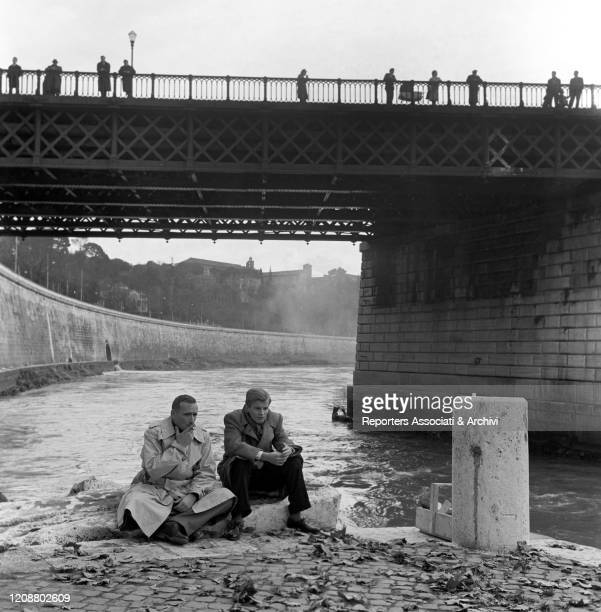 """Italian director Valerio Zurlini sitting by the river under the bridge with French actor Jacques Perrin during a break on the set of the film """"Family..."""