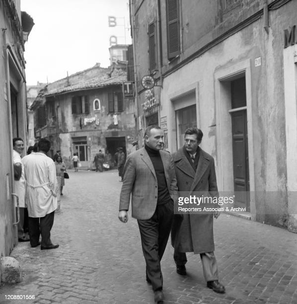 Italian director Valerio Zurlini walking along a street while talking to Italian actor Marcello Mastroianni during a break on the set of the film...