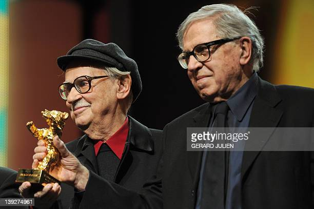Italian directors Vittorio and Paolo Taviani pose with the Golden Bear prize awarded for their film Caesar Must Die on February 18 2012 in Berlin...