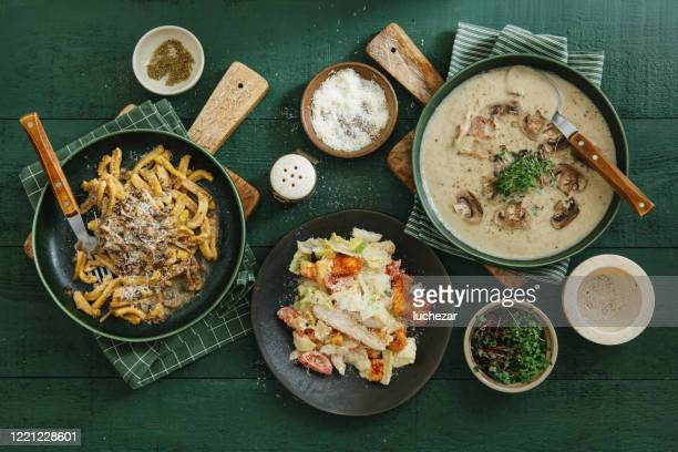 italian dishes. cream of wild mushroom soup and caserecce with wild mushrooms and caesar salad - comfort food stock pictures, royalty-free photos & images
