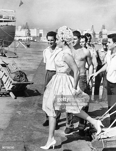 Italian dockworkers stop to admire Liz Taylor arriving from Capri for a holiday before beginning work on 'Cleopatra'.