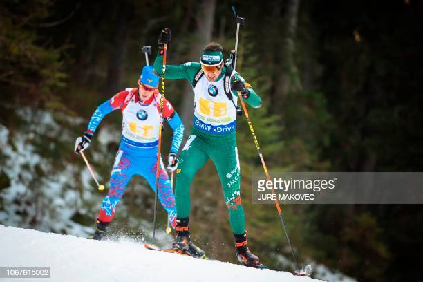 Italian Dominik Windisch and Russian Dmitry Malyshko compete during the Mixed Relay competition of the IBU Biathlon World Cup in Pokljuka on December...