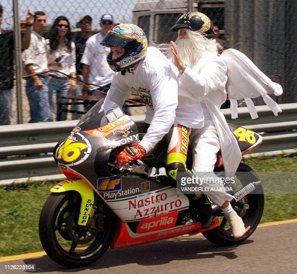 Italian driver Valentino Rossi of team Aprilia rides his cycle with a fellow Italian dressed as an angel after he won in the 250 cc category at the...