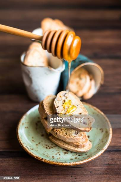 Italian dry cookies cantucci or biscotti with nuts stacked on a dessert plate on a wooden table with honey and honey spoon, selective focus