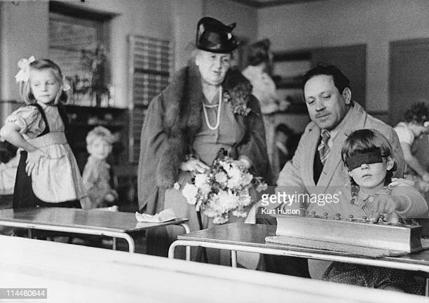 Italian educationist and founder of the Montessori Schools Maria Montessori and her nephew watching a girl working in a classroom in Acton London...