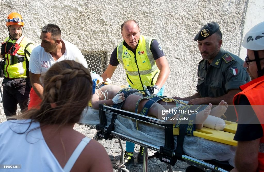 TOPSHOT - Italian emergency workers evacuate, on a stretcher, Mattias, a 7 year-old boy who was trapped by rubble, in Casamicciola Terme, on the Italian island of Ischia, on August 22, 2017, after an earthquake hit the popular Italian tourist island off the coast of Naples, causing several buildings to collapse overnight. Rescuers on the Italian holiday island of Ischia were racing on August 22, 2017 to save the last child trapped by rubble after a magnitude-4.0 earthquake toppled buildings and left two people dead. Firefighters were digging with their bare hands to pull 11-year old Ciro, the last of three brothers buried in the debris, about 13 hours after the quake struck. / AFP PHOTO / Eliano IMPERATO