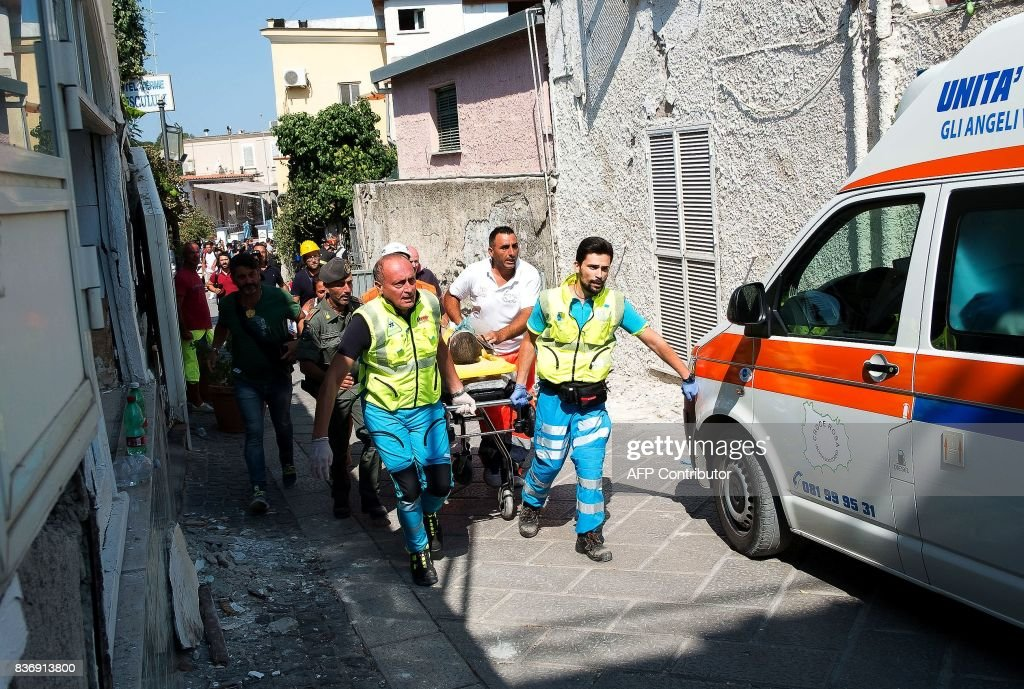 TOPSHOT - Italian emergency workers evacuate on a stretcher Mattias, a 7-year-old boy who was trapped by rubble, in Casamicciola Terme, on the Italian island of Ischia, on August 22, 2017, after an earthquake hit the popular Italian tourist island off the coast of Naples, causing several buildings to collapse overnight. Rescuers on the Italian holiday island of Ischia were racing on August 22, 2017 to save the last child trapped by rubble after a magnitude-4.0 earthquake toppled buildings and left two people dead. Firefighters were digging with their bare hands to pull 11-year old Ciro, the last of three brothers buried in the debris, about 13 hours after the quake struck. / AFP PHOTO / Eliano IMPERATO