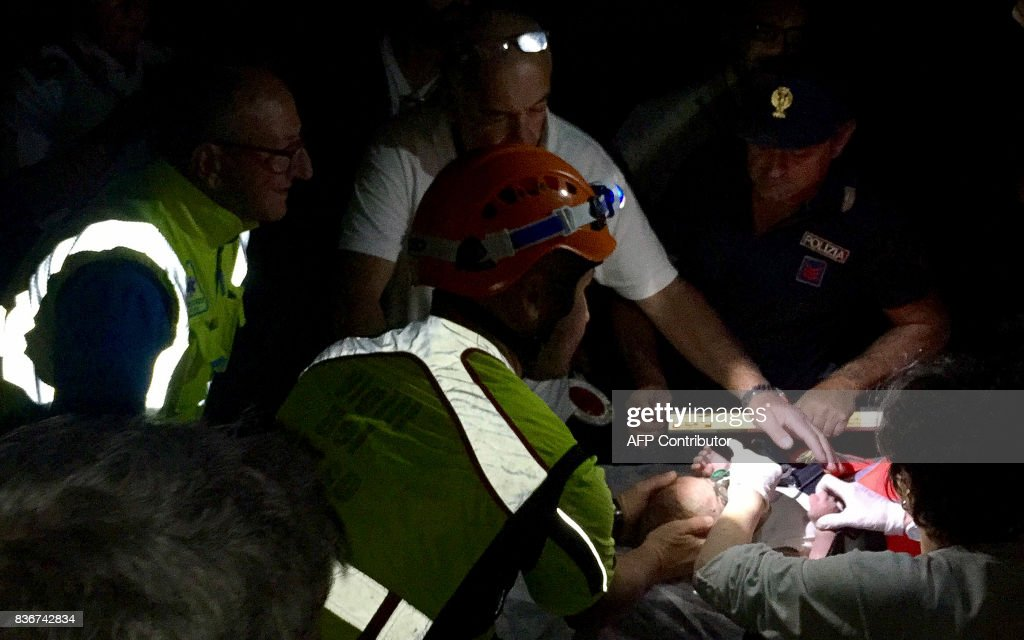 TOPSHOT - Italian emergency workers rescue a baby after an earthquake hit the popular Italian tourist island of Ischia, off the coast of Naples, causing several buildings to collapse overnight on August 21, 2017. A magnitude-4.0 earthquake struck the Italian holiday island of Ischia, causing destruction that left two people dead at peak tourist season, authorities said, as rescue workers struggled early to free two children from the rubble. / AFP PHOTO / Mauro Pagnano