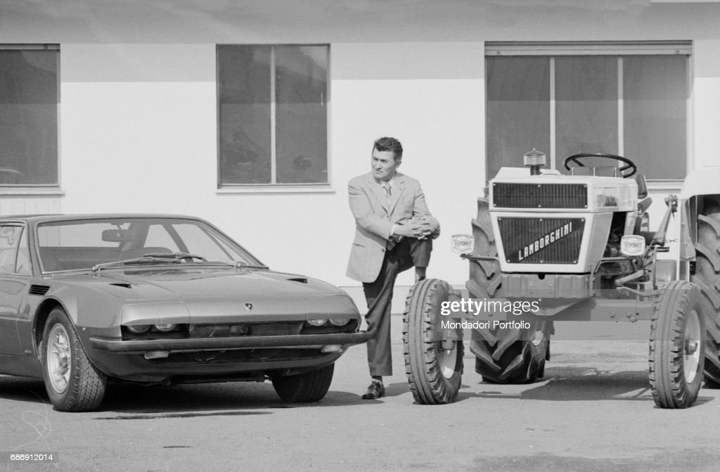 Ferruccio Lamborghini standing between a Lamborghini Jarama and a tractor : News Photo