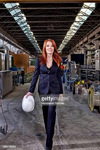 Italian entrepreneur and politician Michela Vittoria Brambilla smiling and walking with a hard hat in the hands at Trafilerie Brambilla Calolziocorte...