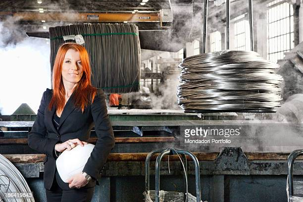 Italian entrepreneur and politician Michela Vittoria Brambilla posing with a hard hat in her hands in front of some steel wires in stack at...