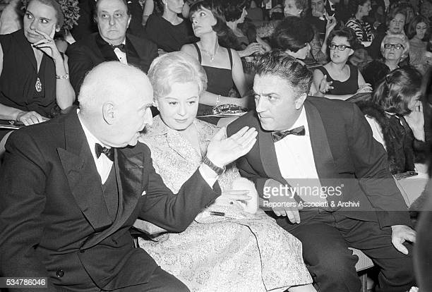 Italian entrepreneur and publisher Angelo Rizzoli talking to Italian actress Giulietta Masina and Italian director Federico Fellini at the premiere...
