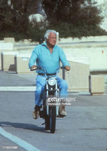 Italian entrepreneur Gianni Agnelli riding a scooter. 1990s