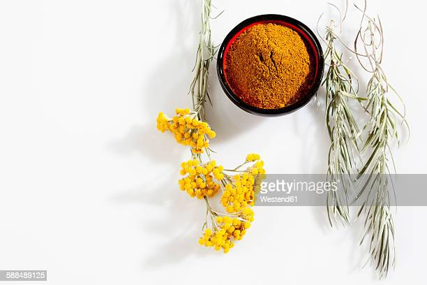 Italian Everlasting and bowl of curry powder on white ground