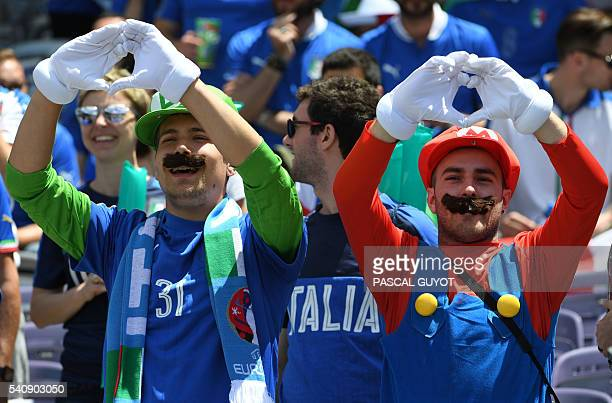 Italian fans dressed up as Super Mario videogame character gesture as they wait for the start of the Euro 2016 group E football match between Italy...