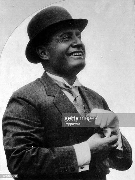 Italian fascist leader Benito Mussolini wearing a hat as he looks up smiling