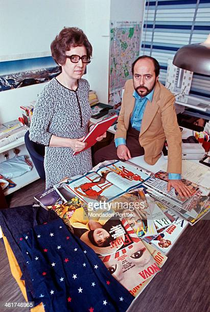 Italian fashion designer and entrepreneur Elio Fiorucci posing in his office with his secretary On the desk fashion magazines and fabrics Milan 1972