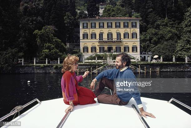 Italian fashion designer Gianni Versace and Lalla Spagnol relaxing on a motor launch in front of Versace's 17th century villa, Villa Fontanelle, at...