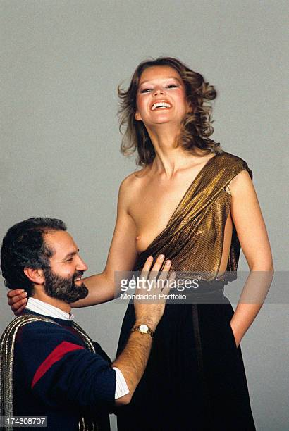 Italian fashion designer Gianni Versace dressing a model with one of his crations 1980s