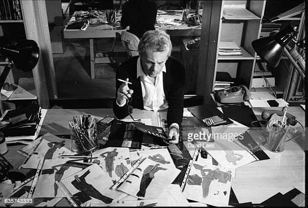 Italian fashion designer Giorgio Armani, born in Piacenza in 1935, examines drawings for new designs.