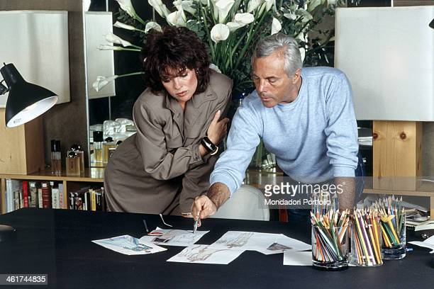 Italian fashion designer Giorgio Armani showing some sketches to American actress Linda Gray. 1983