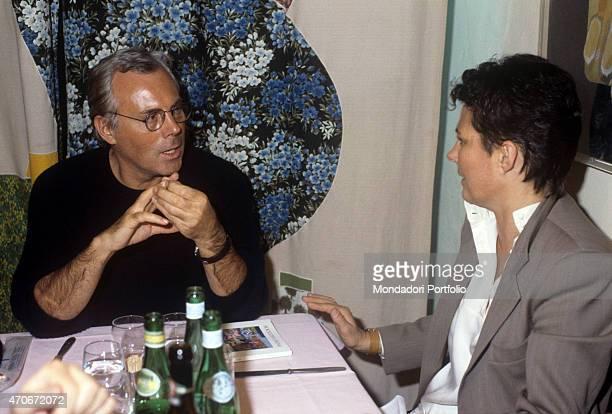 Italian fashion designer Giorgio Armani sitting at the table with his sister Rosanna 1980s