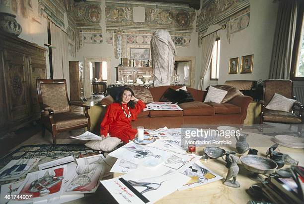 Italian fashion designer Laura Biagiotti sitting on the floor near some sketches in a room of the castle of Marco Simone where she lives Guidonia...