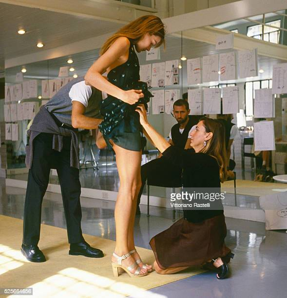 Italian fashion designer Miuccia Prada adjusting clothes on Italian-French top model Carla Bruni.