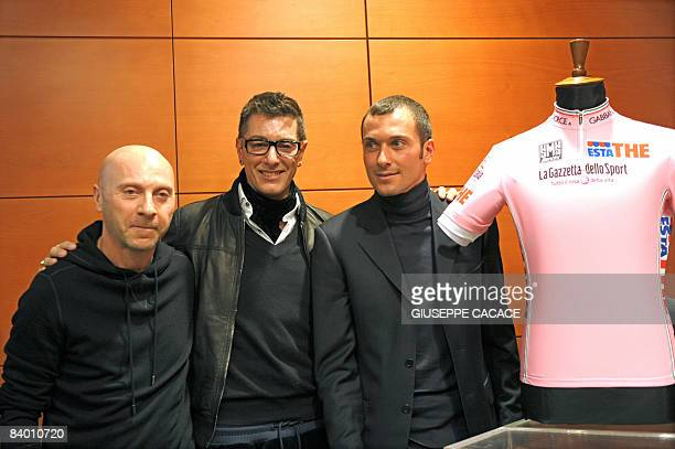 Italian fashion designers Domenico Dolce and Stefano Gabbana pose with rider Ivan Basso during the presentation of the Maglia Rosa the pink jersey...