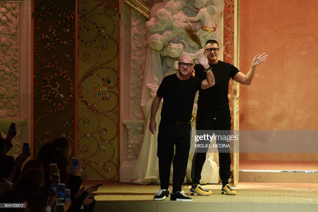 Italian fashion designers Domenico Dolce and Stefano Gabbana acknowledge the audience at the end of their women's Fall/Winter 2018/2019 collection fashion show by Dolce & Gabbana in Milan, on February 25, 2018. / AFP PHOTO / Miguel MEDINA
