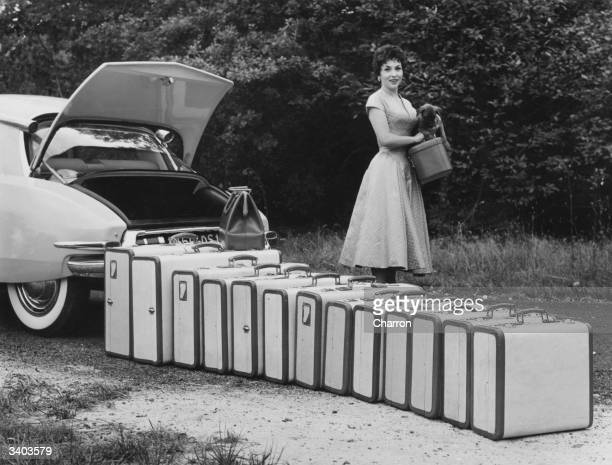 Italian film actress Gina Lollobrigida standing beside a row of suitcases which amazingly all fit into the boot of a Citroen DS 19
