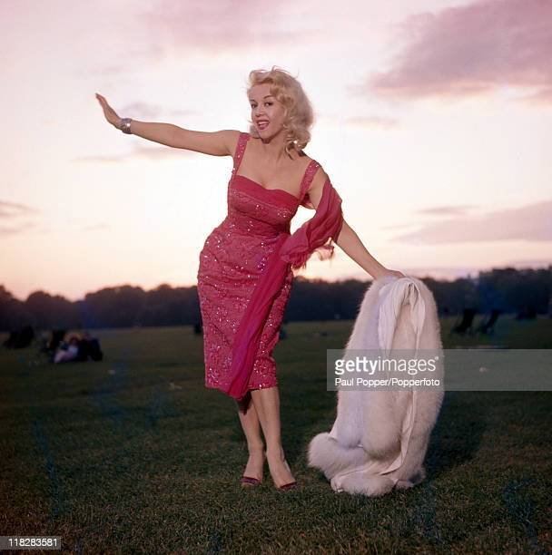 Italian film actress Rosalina Neri vamping Marilyn Monroe in a red sequined dress and white fox stole in a landscape at sunset circa 1960