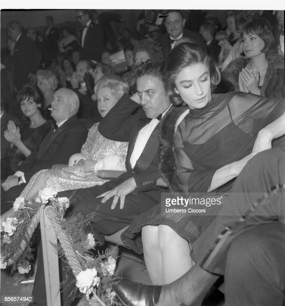 Italian film director Federico Fellini at the 'Cinema Fiamma' in Rome with Angelo Rizzoli Giulietta Masina and Anouk Aimee