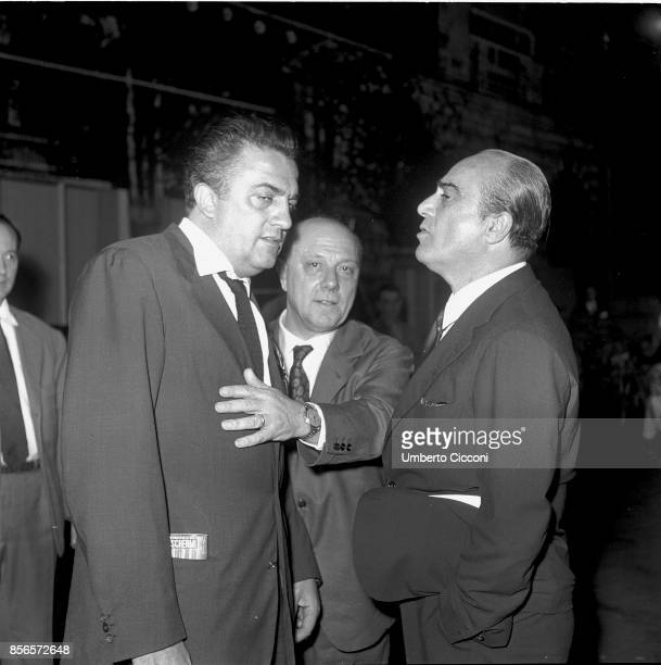 Italian film director Federico Fellini at the cocktail party for the movie 'La Dolce Vita' with film producers Franco Magli and Giuseppe Amato...