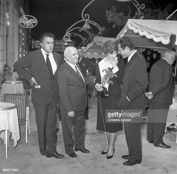 Italian film director Federico Fellini at the cocktail party for the movie 'La Dolce Vita' with film producer Angelo Rizzoli actor Marcello...