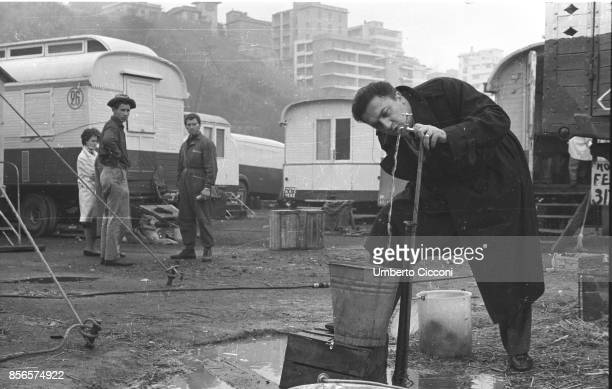 Italian film director Federico Fellini drinks water from the fountain at the 'Orfei Circus' Rome People look at him