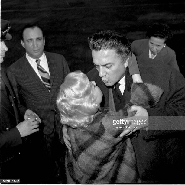 Italian film director Federico Fellini hugs and kisses his wife and actress Giulietta Masina before she leaves for Germany Rome 1959 They are at...