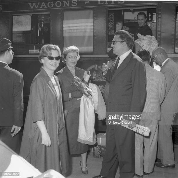 Italian film director Federico Fellini is about to catch a train in Termini Station with his wife and actress Giulietta Masina and lady Tati Rome 1958