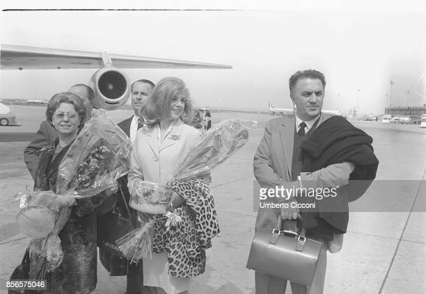 Italian film director Federico Fellini is at Fiumicino Airport with his wife and actress Giulietta Masina and the actress Sandra Milo leaving for...