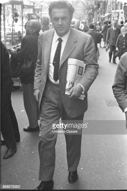 Italian film director Federico Fellini is walking in Via Veneto holding a newspaper Rome 1963