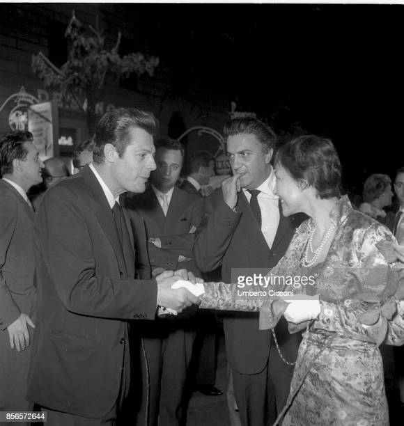 Italian film director Federico Fellini is with Actor Marcello Mastroianni while he shacks the hand with actress Luise Rainer at the cocktail party...