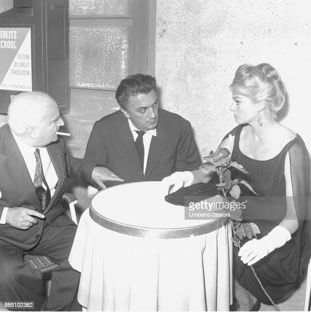 Italian film director Federico Fellini is with actress Anita Ekberg and film producer and publisher Angelo Rizzoli at the cocktail party for 'La...