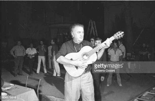 Italian film director Federico Fellini plays a guitar while filming 'Roma' Cinecittà Studios Rome 1971