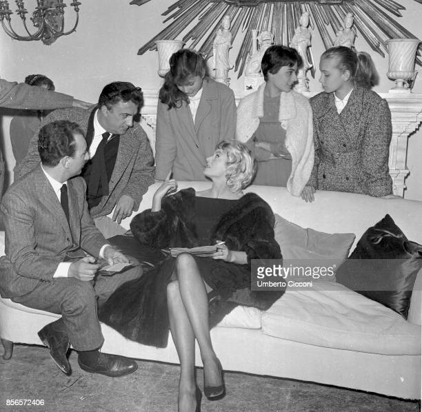 Italian film director Federico Fellini talks to Swedish actress Anita Ekberg actor Renato Tagliani actress Valeria Ciangottini and two more young...