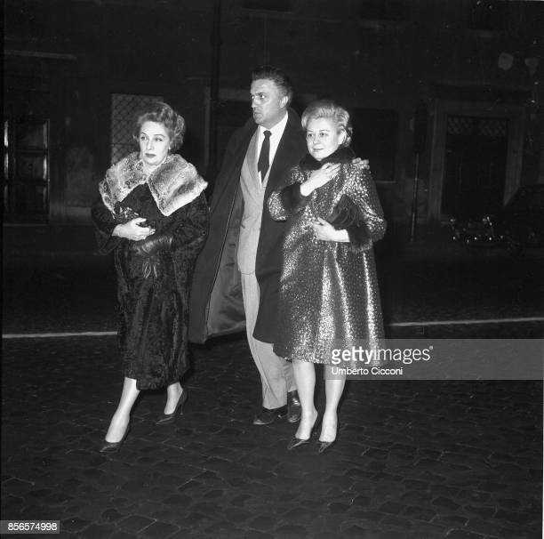 Italian film director Federico Fellini walks in nighttime in Via Veneto with his wife and actress Giulietta Masina and the actress Andreina Pagnani...