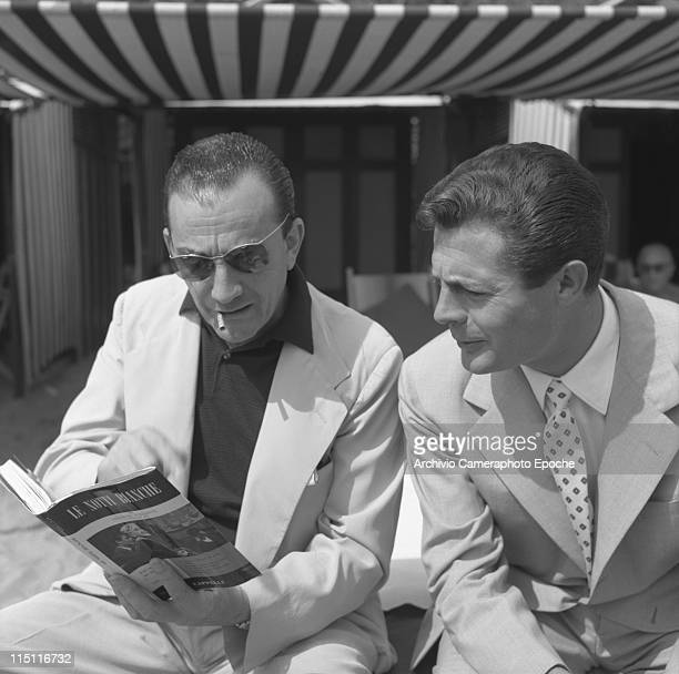 Italian film director Luchino Visconti, wearing a fair suit, a striped shirt and sunglasses, smoking a cigarette, holding a book about his movie...