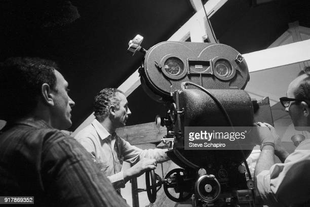 Italian film director Michelangelo Antonioni along with unidentified crew members stands behind the camera on the set of his film 'BlowUp' London...