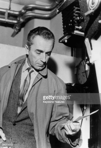 Italian film director Michelangelo Antonioni visits a Fleet Street photographic press agency whilst in London to film the hip mystery 'Blow Up'