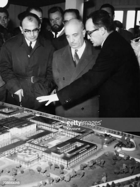 Italian film producer Dino De Laurentiis discussing an architectural model of his planned 'Dinocitta' film studio with Italian Prime Minister...