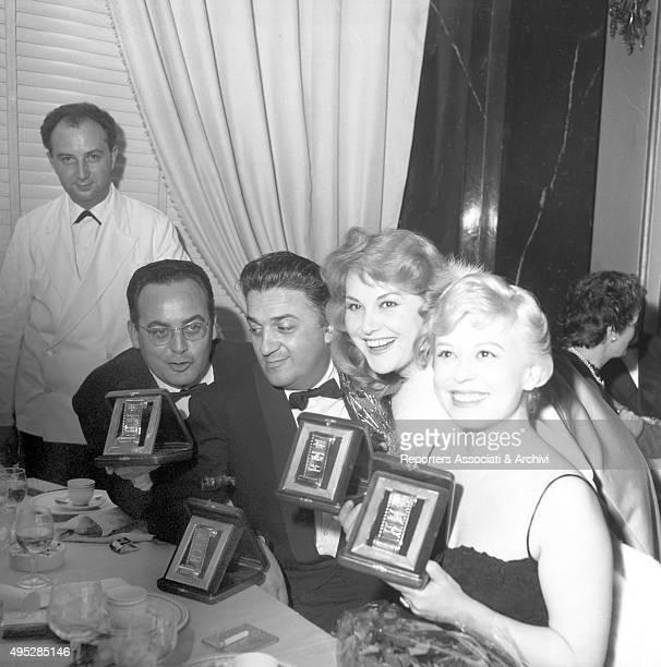 Italian film producer Dino De Laurentiis Italian director Federico Fellini and Italian actresses Franca Marzi and Giulietta Masina showing the Nastri...